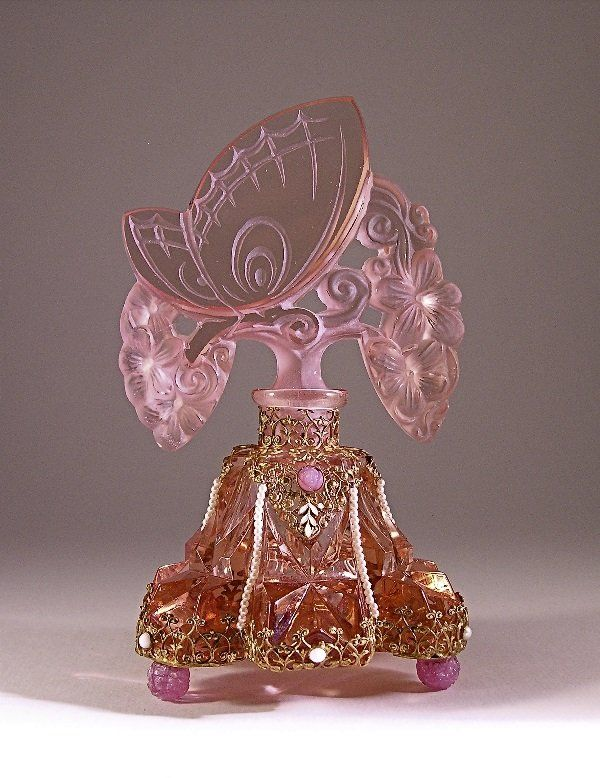 1920s perfume bottle and stopper in pink crystal with enamel and jeweled metalwork, glass feet, dauber stub. Czech mark on metal. 6 7/8 in. Sold for $4000 in 2009