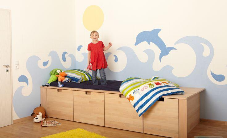 Wandgestaltung mit Rollputz: Beschwingte Wellen und ein glitzernder Delfin als Wandmalerei zaubern Sonnenlaune an die Wand im Kinderzimmer