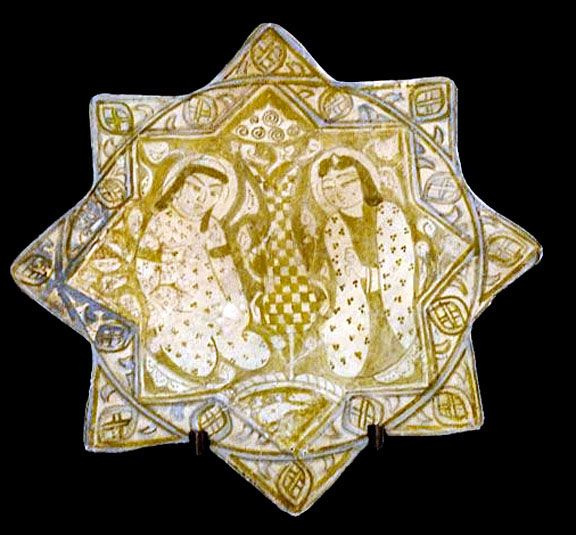 Lusterware Star Tile  Two Kneeling Human Figures with Calligraphy Border.  Lusterware, a type of ceramic named after lustrous, glinting finish that was achieved by a particular kind of glaze.  The town of Kashan gave its name to the Persian word for tile; kashi. It was one of the principal and most famous centers for the production of fine pottery and tiles between the 12th and 14th centuries.