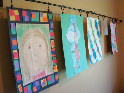 hanging your child's art work. Hang it: Set up curtain rods and hang the artwork using the clips. You could set up one long one or multiple rows if your space is more narrow. An even cheaper option is to use a clothesline and clothespins to hang everything. Just use a screw-in hook to attach the clothesline to each side of the wall.