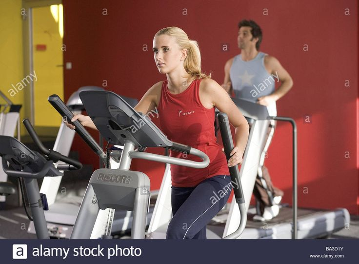 Gym ergo-meter woman Crosstrainer man conveyor belt people sport fitness gymnastics health beauty Workout body-consciousness Stock Photo