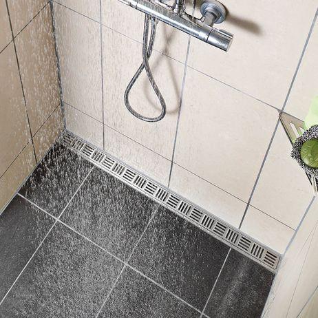 Tässä kylpyhuoneessa on seinän viereen asennettu unidrain® ClassicLine -linjalattiakaivo. Kun lattian kaato tarvitsee tehdä vain yhteen suuntaan, on suurten lattialaattojen käyttäminen mahdollista.  Kaivon malli: ClassicLine linja, Inca-ritilällä.