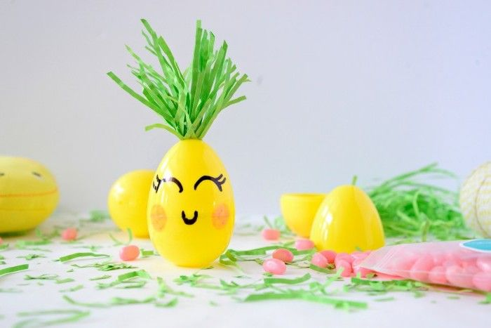 plastic yellow easter egg, decorated to look like a pineapple, with green felt leaves, and smiling face, drawn in marker, easter grass and candies, and other plastic yellow eggs nearby