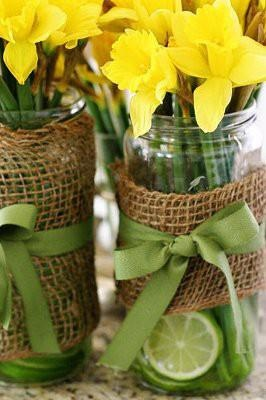 Spring dandelions in a mason jar wrapped with burlap and ribbon and limes added to the water