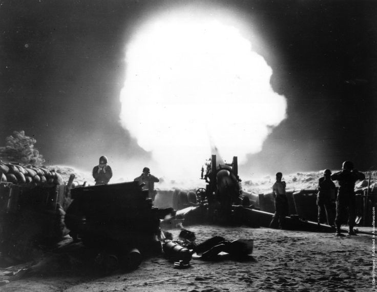 A dramatic shot of 155mm Howitzer fire during night action in the Korean War.  1952: Photo