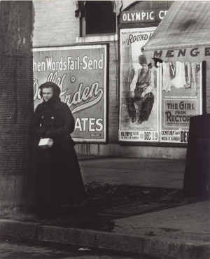 """A woman bundled in winter wear stands at an unidentified street corner in front of advertisements for the movies """"The Round Up"""" at the Olympic Theater and """"The Girl from Rector's"""" showing at the Century Theater. (1917)"""