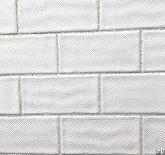 Белая плитка в форме кирпичика с резным узором