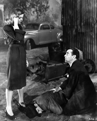 "Director Howard Hawks' ""The Big Sleep"" (1946): Philip Marlowe earlier tries to get Vivian to let him loose from being tied up, memorably saying, 'Camino is going to knock my teeth out and then kick me in the stomach for mumbling'. Camino here lies dead at his feet...(Bogie and Bacall shown.)"