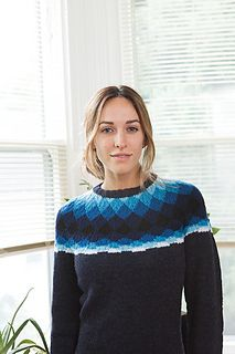 Bold and modern, a pattern of diamonds seems to melt into the body of this yoked colorwork pullover. Worked from the bottom up in Stockinette Stitch, the Phased Yoke Pullover begins with ribbing along the bottom edge of the sweater as well as along the cuffs. The yoke of the sweater is shaped to the neckline with cleverly hidden decreases. After the neck steek has been cut, a simple rolled rib collar finishes off the neckline.
