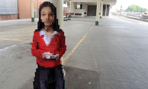 Пикселова скулптура на девојче поставена на железничка станица