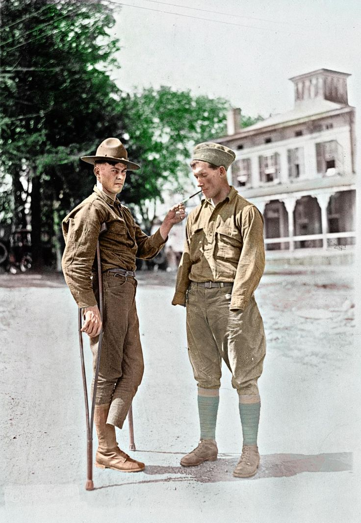 At Walter Reed Hospital, a soldier who is missing a foot lights a cigarette for another soldier who is missing both arms, circa 1918.