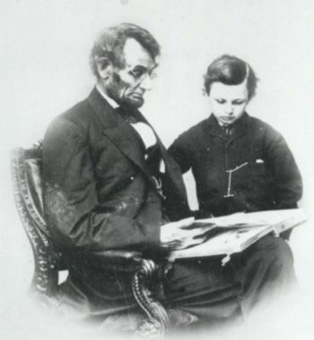 Lincoln reading to son Tad; one of only known photographs of Lincoln with glasses