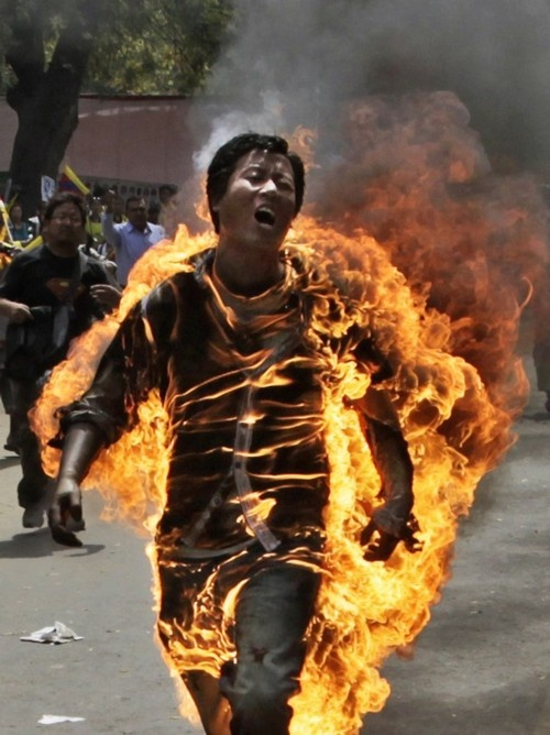 """""""A Tibetan man, identified as Jampa Yeshi, screams as he runs engulfed in flames after self-immolating at a protest in New Delhi, India, ahead of Chinese President Hu Jintao's visit to the country Monday, March 26, 2012.""""  (AP Photo/Manish Swarup)"""