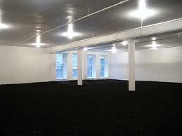"""Earth Room. Walter Di Maria, 1980. Es una muestra de Land Art, 127 mil kilos de arena osura dentro de una sala de paredes y techo blancos. La novedad es esta tendencia en sí, que rompe con las normas de hacer arte en un simple lienzo, tabla o pared, adiós a las """"simples esculturas"""" o cualquier otra forma tradicional de lo que entendíamos por arte. Ahora se considera que cualquier transformación del hombre en la tierra, es arte. La obra aporta un """"trozo de campo"""" en medio de Nueva York."""