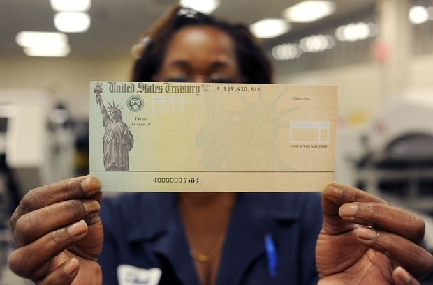 Treasury employee Linda Tarkenton of Philadelphia holds a blank U.S. Treasury check before it's run through a printer at the U.S. Treasury printing facility. Photo by William Thomas Cain/Getty Images. LARRY KOTLIKOFF