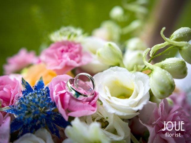 Malá letní svatba v přírodě, snubní prsteny na kytici v detailu