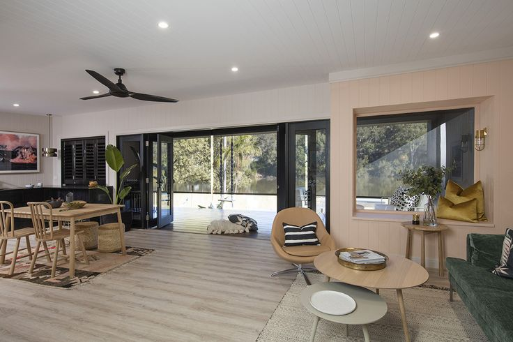 Lounge and view out deck: Luxaflex Evo Drop Awnings - Three Birds Renovations House 7, River Shack