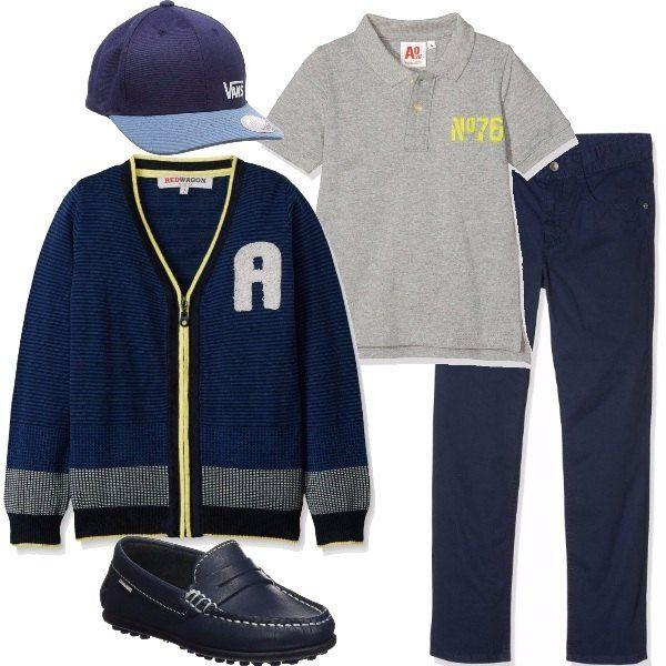Pantalone blu di cotone, polo grigia, cardigan blu anch'esso di cotone con scollo a V e patch ricamato. Concludiamo l'oufit con mocassino di pelle blu e cappellino con visiera.