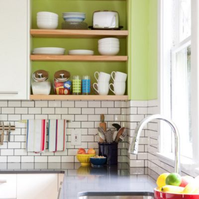 Keep subway tile from looking too industrial by incorporating bright colors into shelving and other elements.
