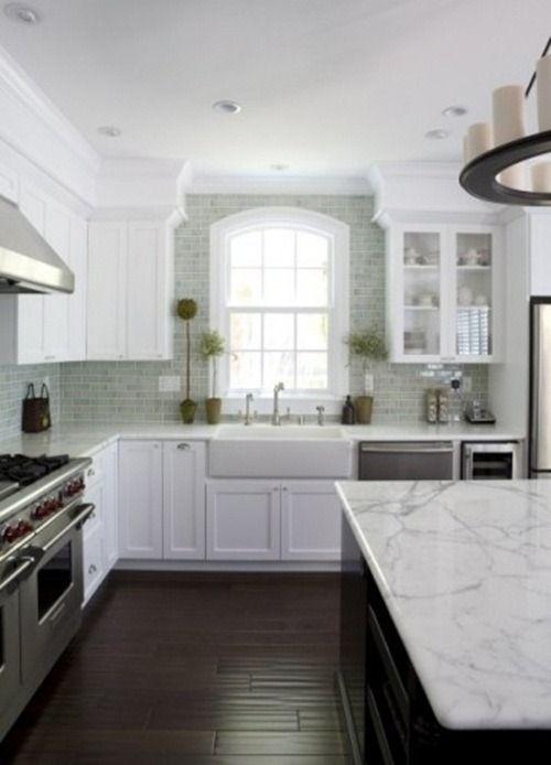 colors; dark floor, dark island, white cabinets, grey/light backsplash