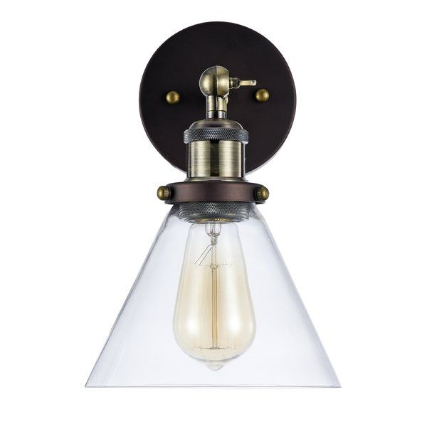 Masterfully mixing clean-lined design with rustic details, this charming one-light wall sconce is the perfect piece to illuminate your space in understated style. Featuring steel construction in a timeless oil-rubbed bronze finish, this charismatic design includes a circular backplate, an angular arm, and a stylishly slanted seeded glass shade around a fashionable Edison bulb. For an upscale, tailored look in your master bedroom, install this light over a trestle-base nightstand on each side…