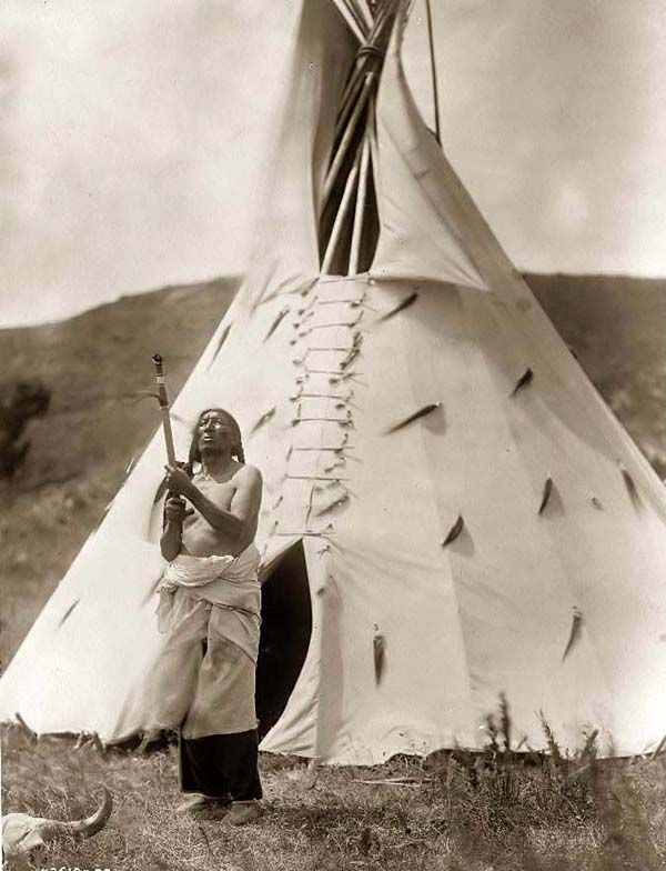 You are looking at an intriguing picture of Slow Bull, a Dakota Sioux Medicine Man. It was taken in 1907 by Edward S. Curtis.    The picture presents the Medicine Man standing outside his tipi gazing upward, apparently in Prayer.    We have created this collection of pictures primarily to serve as an easy to access educational tool. Contact curator@old-picture.com.    Image ID# 7D59DF2A