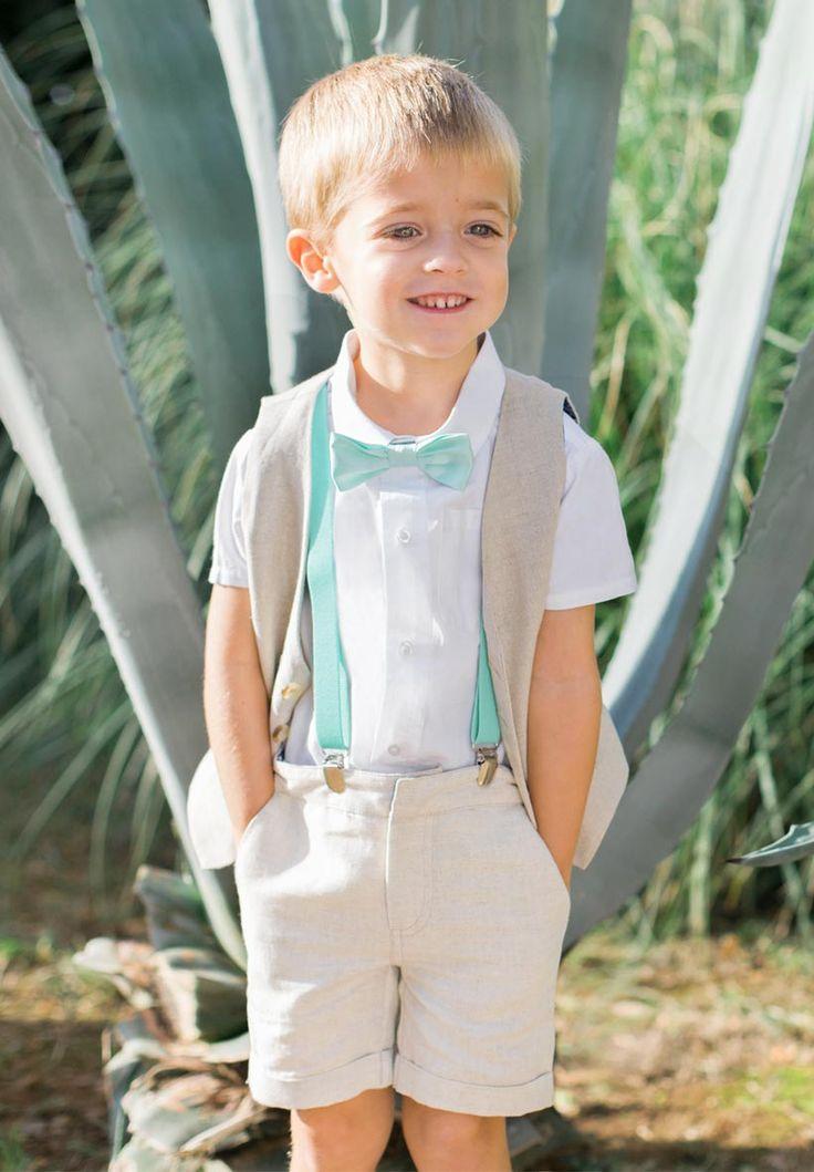 Ce charmant garçon d'honneur porte notre ensemble en lin accompagné de bretelles Marcel vert d'eau ainsi qu'un noeud papillon Roméo vert d'eau également