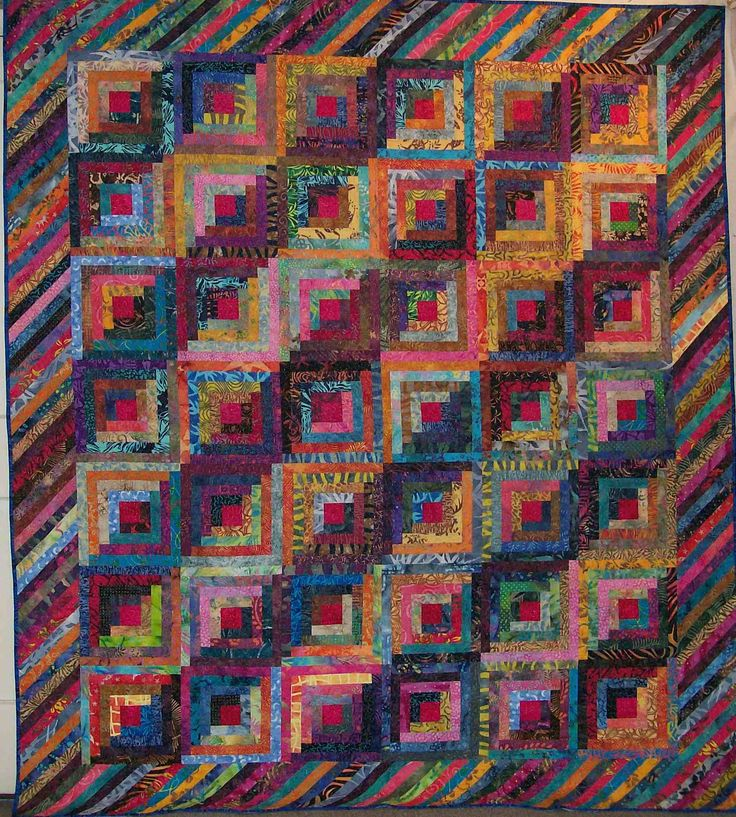 Batiks.  Very nice the way the angles in the border match the angles of the straight furrow setting.