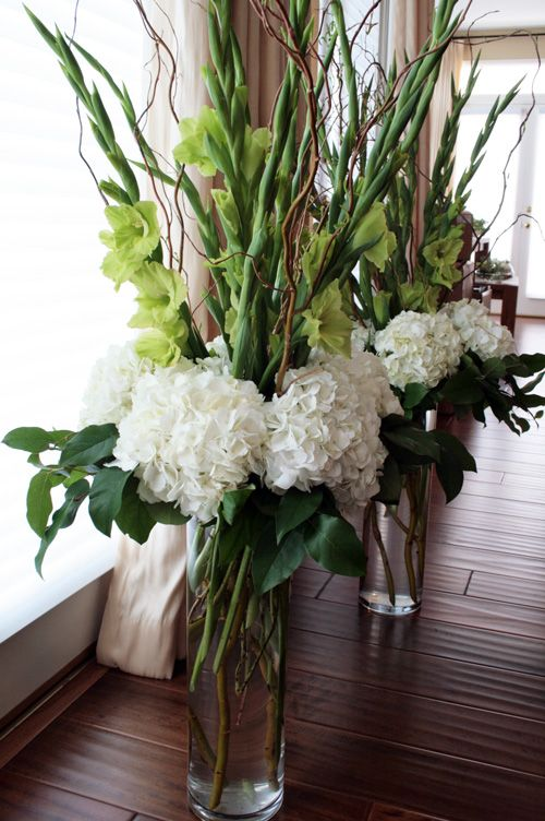 Tall arrangements for the church made of velvety green gladiolas and white fluffy hydrangea.
