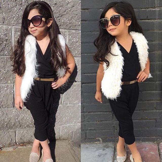 White fur vest black pant romper with tan belt sunglasses