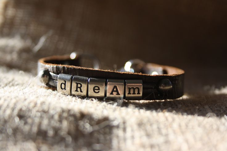 """A 3/8"""" leather bracelet dyed dark brown with the word """"Dream"""" in metal ribbon letters.  Finished with a spring snap closure.  http://shop.sydenhamhillfarm.ca/products/dream-bracelet"""