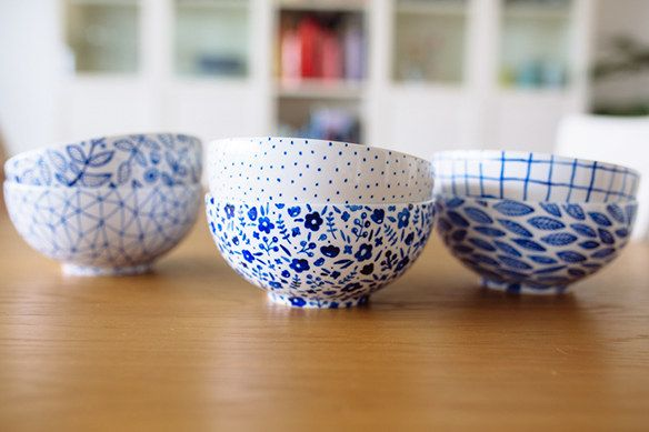 Male mit Porzellan-Malstiften Muster auf 365+-Schüsseln.