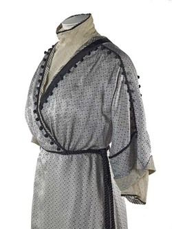 Dress A pattern of this dress is included in Janet Arnolds 'Patterns of Fashion: Englishwomen's dress and their construction c. 1860-1940 on page 60. Arnold describes the gown as a  'day dress in silver-grey silk foulard with a tiny striped print of white cigar shapes with black spots at the ends. The gilet front is in spotted ivory net to match the sleeve end and cuffs. The raised waistline is clearly definted by the black twisted silk cord sash. The left side of the skirt has a panel of…
