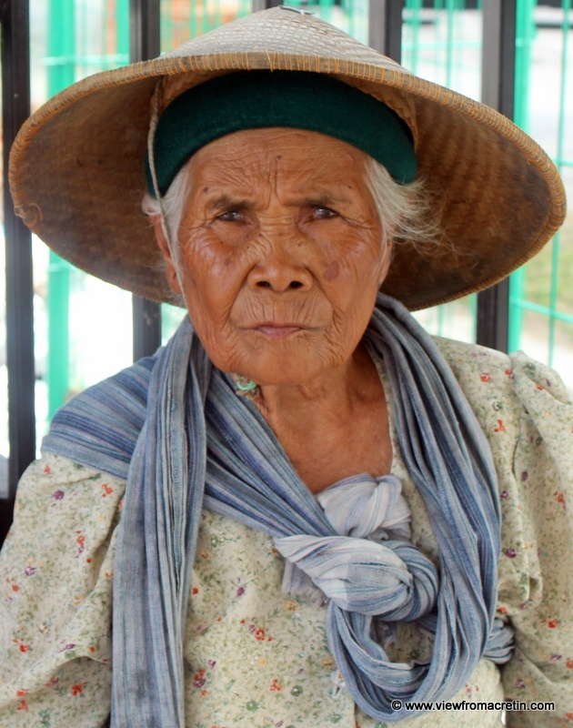 an old Indonesian woman  she's wearing a traditional cap named caping. it protects her from the sunbeam