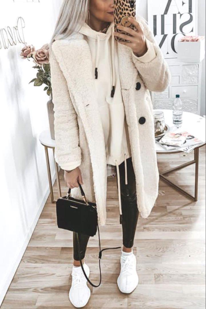 Damenmode im Herbst / Winter mit einem weißen Mantel, einem beigefarbenen Sweatshirt und weißen Turnschuhen.