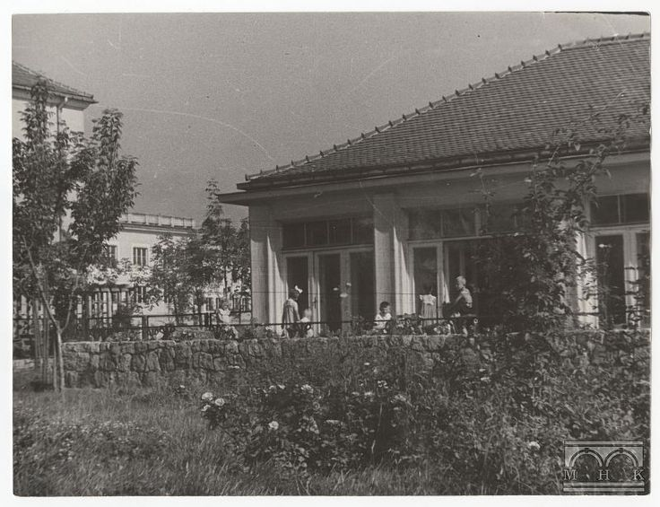 Fragment kindergarten project Marta Ingarden, 1951, Nowa Huta (Cracow). The edge of the building storey kindergarten, standing in the garden of the small foundation. In the foreground visible lawn with flower rabatkami and trees. On the terrace playing with a group of about 5 children. In the background you can see two buildings. When the frame of the frame on the left side of the building with a sloping roof and behind him, the attic estate Willowe.