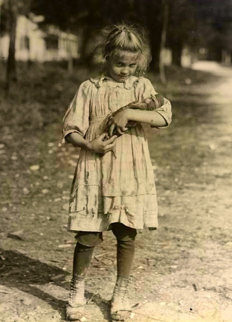 Look at how dirty and disheveled this little girl looks, yet see how she tenderly holds her doll.