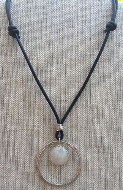 Black leather with a hammered Sterling silver ring and a Moonstone pendant. Adjustable length.