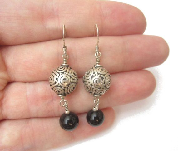 Beautiful bali silver, accented with smooth black onyx makes for a gorgeous pair of day or night earrings! Purchase them for your ears today!