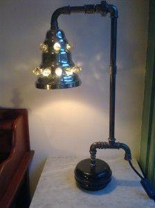 Cette lampe de bureau à l'allure tubulaire est réalisée à partir d'une base en marbre noir. Le corps est constitué de tubes et raccords de plomberie et l'abat-jour est une vieille suspension en acier chromé et boules de verre à facettes. Hauteur : 59...