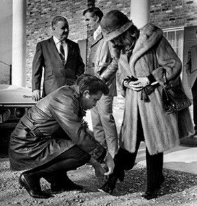 Johnny Cash kneels to buckle the shoe of his wife June Carter Cash in front of the Plantation Dinner Club, before signing contracts to buy to buy the theater in Hendersonville, Tenn.-------12-16-1969.