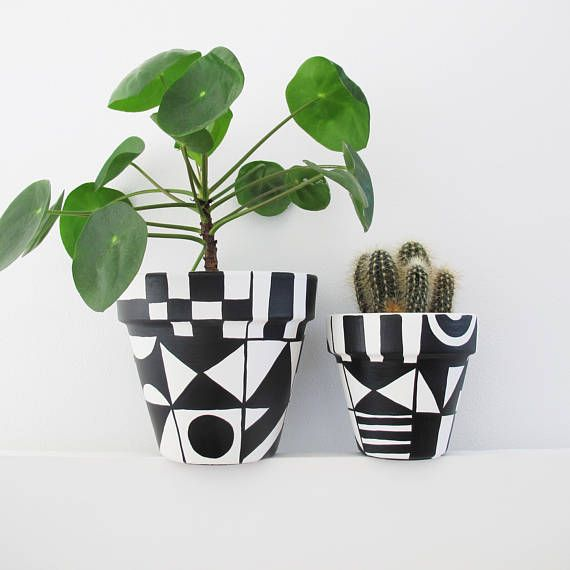 An Intricately Hand Painted Plant Pot With Black And White Tiled