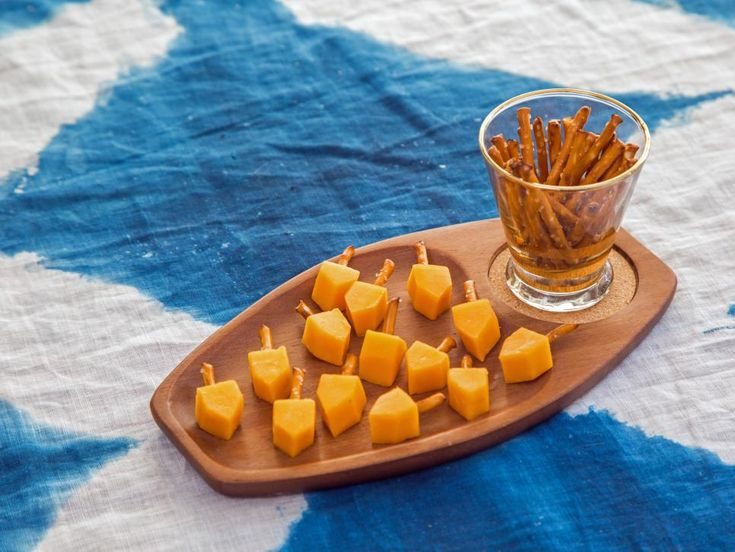 Cut cheddar cheese sticks into squares, and snip off the ends so they resemble dreidels. Use a toothpick to make a hole in the top of the cheese, and place a small pretzel stick inside.