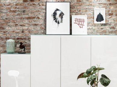 Proste geometryczne białe szafki stojące w salonie przy ścianie z czerwonej patynowanej cegły (27631)