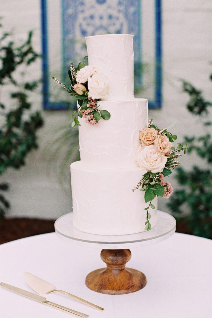 weiße gestufte Hochzeitstorte mit frischen Blumen Fotografie: Carmen Santorelli   – Weddings