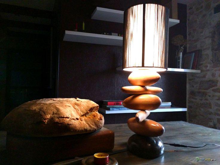 Grande lampe de galets de bois glacés sous abat jour noir à fil. Les galets sont arondis ou/et effilés à la main. Chaque galet est unique tant par sa forme, ses dessins, ses couleurs.  Bois : La lampe est en galets en bois réalisés entièrement à la main à partir de bois de récupération. Finition glacée de luxe brillante.  Eclairage : Réalisé avec 1 ampoule LED 12 volts à 360 degré de 27 Leds. Rendu : 6000°K Consommation : 6.5W, rendu : 45W