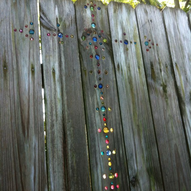 I had seen the random marble placement of marbles in a fence and decided to create a cross. My awesome husband went to craft store with me where we found no marbles and decided to go with glass beads. We cut a couple of bead strands that were made for necklaces and bought a box of mixed beads. Awesome husband continued awesomeness by drilling all the holes for me after we drew a cross with a level for only a simple outline. The rest was freehand.  Try it! It's fun and when the light gets…
