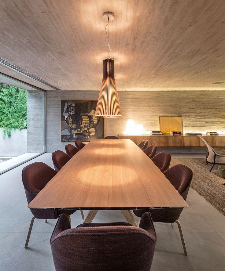 Casa, decoração de casa, modernismo. Correr de madeira e cinza com luz natural. Na sala de jantar mesa retangular de madeira cadeira estofada roxa.