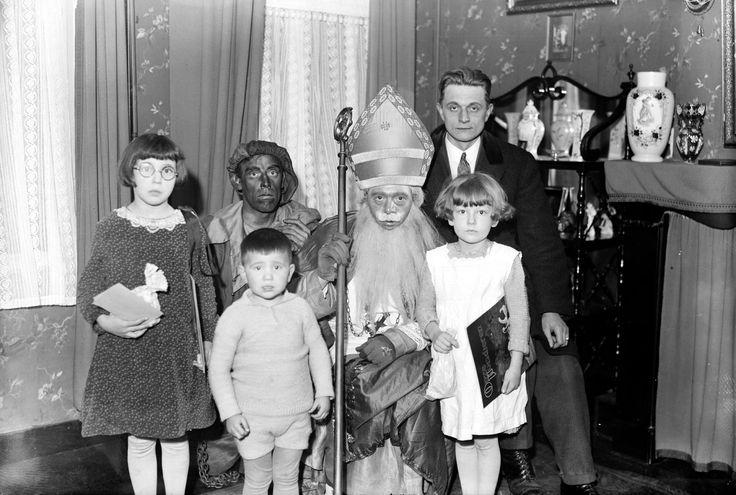 St. Nicolaas en Zwarte Piet op bezoek bij huisgezin, 1930 Den Bosch. Als je goed kijkt zie je bij Piet zijn knie een ketting!