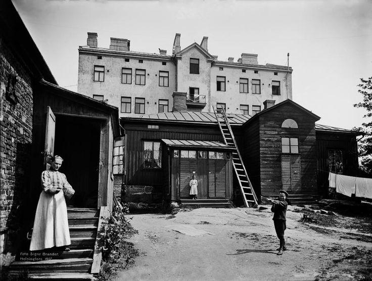 Muuttuvaa kaupunkia. Korkeavuorenkatu 13 pihan puolelta, taustalla kivitalo Kasarmikatu 14. Kuva  Signe Brander, 1907. Helsingin kaupunginmuseo.